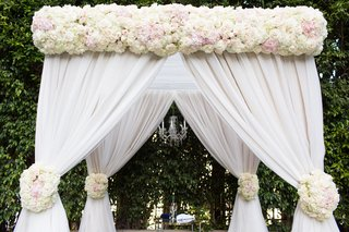 chuppah-with-blush-and-ivory-flowers-and-white-drapery