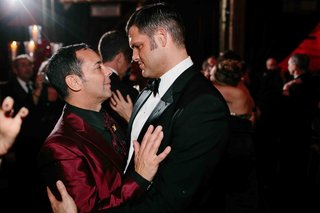 matthew-christopher-couture-wedding-gown-designer-in-a-black-tuxedo-dances-with-his-groom