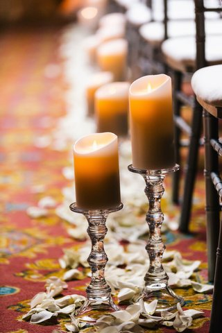 candles-on-stands-with-rose-petals-to-line-aisle-for-wedding-ceremony