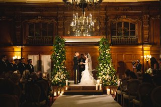 wedding-ceremony-wood-panel-ballroom-chuppah-greenery-white-flowers-candle-chandelier-aisle-runner