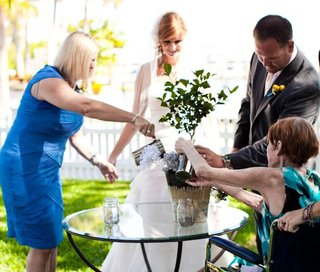 bride-and-groom-with-mothers-watering-small-tree