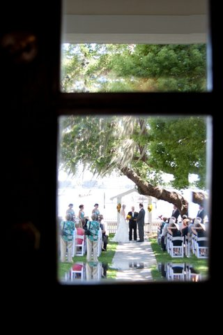 artistic-photo-of-wedding-ceremony-through-window