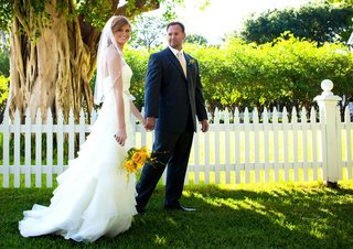 bride-and-groom-in-front-of-white-picket-fence