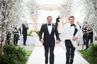 same-sex-wedding-formal-opulent-san-diego-wedding-tuxedo-holding-hands-bow-ties-chuppah-white-aisle