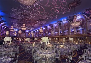 silver-chairs-with-purple-cushions-and-tall-ivory-centerpieces-with-scroll-gobo-on-ceiling