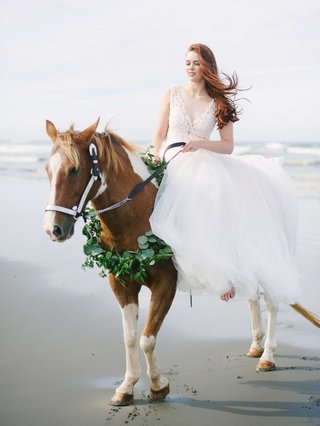 bride-rode-a-horse-with-a-green-wreath-garland-around-its-neck-on-the-beach-in-her-wedding-gown