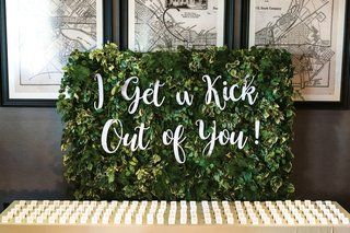 escort-card-table-with-small-greenery-wall-behind-with-i-get-a-kick-out-of-you-in-laser-cut-letter