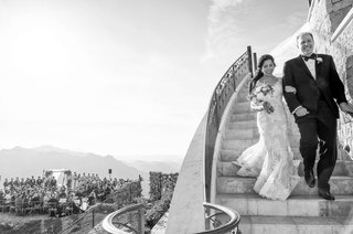 black-and-white-photo-of-bride-in-monique-lhuillier-wedding-dress-walking-down-stairs-with-father