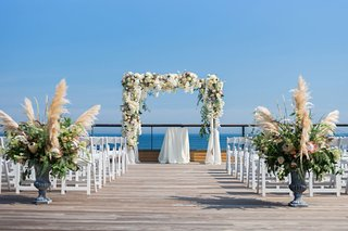 montauk-new-york-wedding-ceremony-desk-pampas-grass-greenery-white-flowers-white-chairs