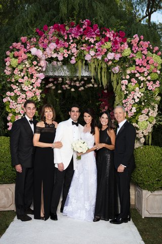wedding-portrait-bride-and-groom-in-white-with-parents-under-chuppah-wearing-black-gowns-tuxes