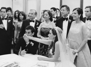 black-and-white-photo-of-groom-kissing-brides-hand-at-ketubah-signing-ceremony-before-wedding