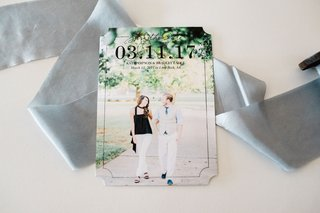 die-cut-save-the-date-card-on-grey-ribbon-with-engagement-photo-of-couple-walking-outside-large-date