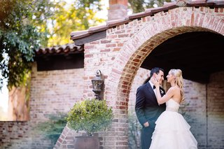 bride-in-a-strapless-hayley-paige-dress-with-tiered-skirt-beaded-belt-laughs-with-groom