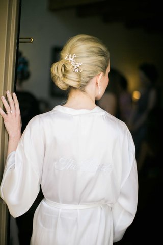 bride-shows-off-her-bun-hairstyle-and-hairpiece-with-crystals-in-bridal-robe-getting-ready