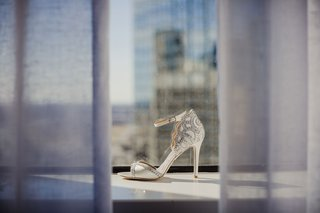 wedding-shoe-in-window-sill-curtain-peep-toe-style-ankle-strap-metallic-details-silver