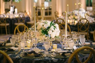 wedding-reception-round-table-short-centerpiece-tall-taper-candles-navy-blue-linens-gold-rim-charger