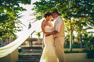 a-bride-and-groom-in-full-wedding-attire-embrace-one-another-in-their-outdoor-wedding-space