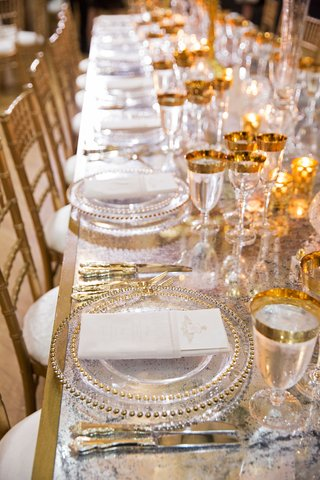 wedding-reception-long-table-mirror-gold-base-gold-chairs-glassware-charger-beaded