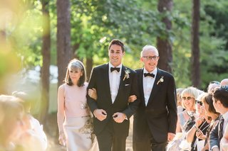 groom-in-tuxedo-and-rustic-boutonniere-walking-down-aisle-outdoor-wedding-with-mother-father-jewish