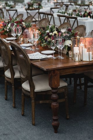 wedding-reception-wood-table-no-linens-low-centerpiece-fall-flowers-brass-candle-votives-vase-cane