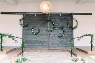 hoop-wreaths-with-greenery-and-bannister-with-greenery-as-wedding-ceremony-backdrop