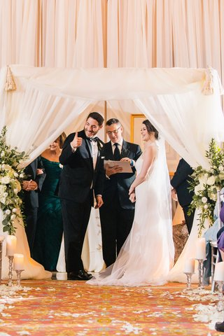 bride-in-lela-rose-wedding-dress-groom-in-michael-kors-tuxedo-thumbs-up-at-jewish-ceremony