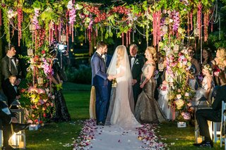 bride-in-anne-barge-wedding-dress-with-groom-in-navy-suit-under-greenery-chuppah-with-flowers