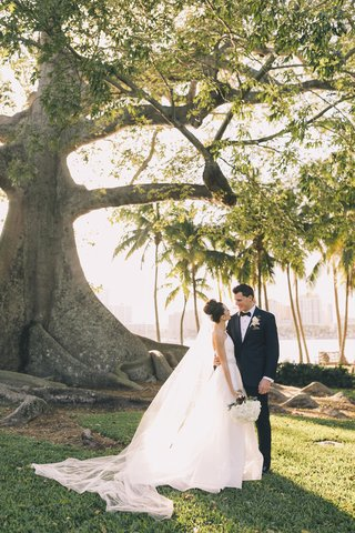 bride-in-romona-keveza-cathedral-veil-large-sock-bun-palm-beach-wedding-groom-in-tuxedo