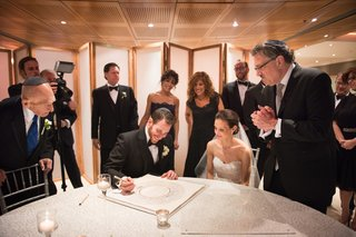 a-jewish-bride-and-groom-signing-the-ketubah-with-friends-and-family-around-before-ceremony