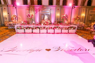 white-dance-floor-with-couples-names-and-heart-in-front-of-head-table-and-cake-pink-lighting