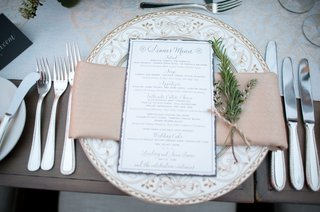 white-plate-with-ornate-design-and-blue-menu-card-calligraphy-greenery-twine-runner