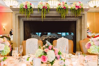wedding-reception-fireplace-head-table-with-mr-and-mrs-signs-chair-covers-pink-green-white-flowers