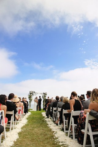 grass-wedding-aisle-with-white-flower-petals-and-rustic-chuppah