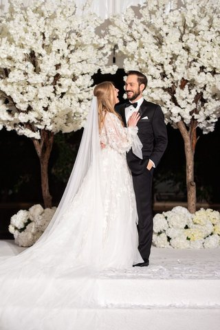 bride-in-long-sleeve-marchesa-wedding-dress-groom-in-tuxedo-white-cherry-blossom-trees-white-stage