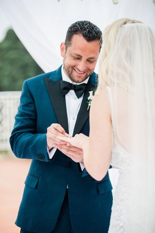 groom-in-navy-brooks-brothers-tuxedo-putting-ring-on-brides-finger-during-the-ceremony
