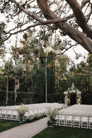 wedding-ceremony-white-chairs-white-flowers-greenery-lights-hanging-from-trees-twinkle-lights-string