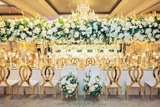 wedding-reception-gold-chairs-flower-bride-groom-chairs-tall-centerpiece-chandelier-modern-gold