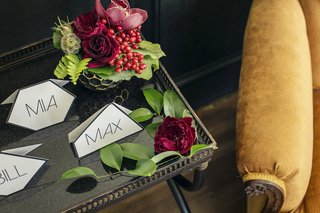 wedding-reception-place-cards-in-geometric-forms-on-table-with-greenery-red-roses-orchids