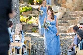 bridesmaids-dressed-in-blue-walk-down-stone-and-gravel-aisle