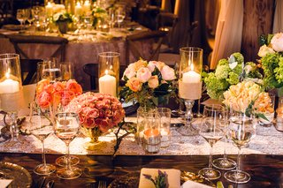 flowers-in-gold-vases-by-variety-amongst-candles-on-a-wooden-table