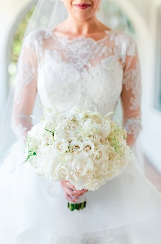 ivory-bridal-bouquet-with-roses-and-peonies-held-by-bride-in-lace-ball-gown