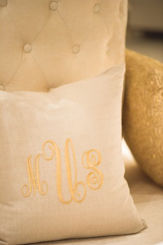wedding-reception-with-throw-pillow-with-gold-monogram-on-elegant-sofa