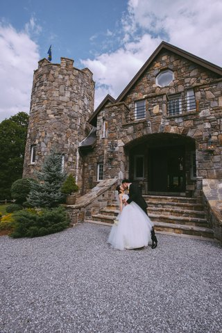 man-dipping-wife-in-front-of-stone-castle-on-gravel