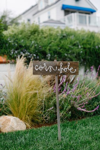 waterfront-wedding-lawn-with-cornhole-written-on-a-weathered-wood-sign