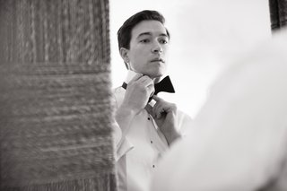 black-and-white-photo-of-groom-putting-on-his-bow-tie
