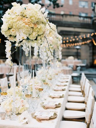 wedding-reception-tall-centerpiece-ivory-flowers-pink-linen-napkins-gold-details-taper-candles-ivory