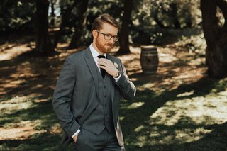 groom-with-glasses-and-beard-in-three-piece-grey-suit-adjusting-his-black-tie