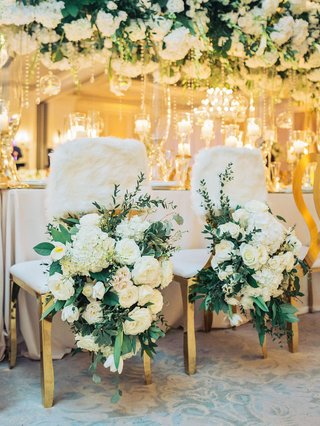 wedding-reception-head-table-bride-groom-chairs-white-flowers-greenery-faux-fur-wrap-chair-cover