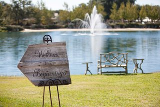 wooden-directional-sign-on-wrought-iron-easel-with-words-welcome-to-our-beginning-next-to-lake