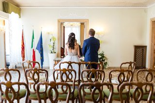 bride-and-groom-facing-officiant-wedding-ceremony-in-venice-italy-at-palazzo-palace-flags-minimal